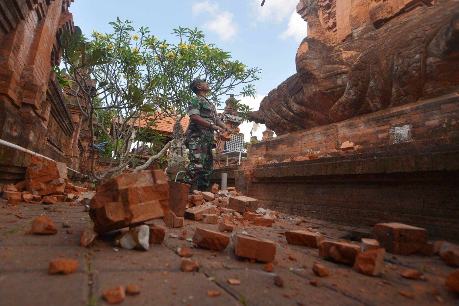 An Indonesian soldier looks at a Hindu temple damaged following an earthquake in Denpasar, Bali, Indonesia