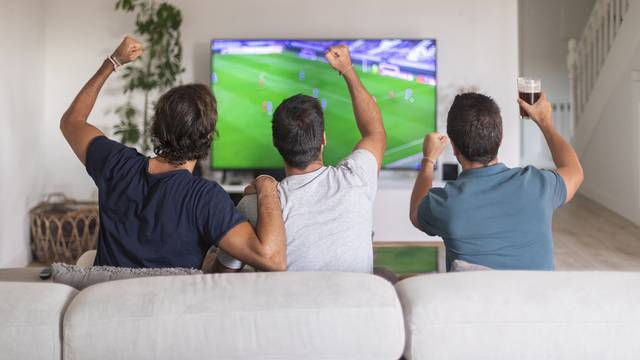 Three friends watching a soccer game at home drinking beer