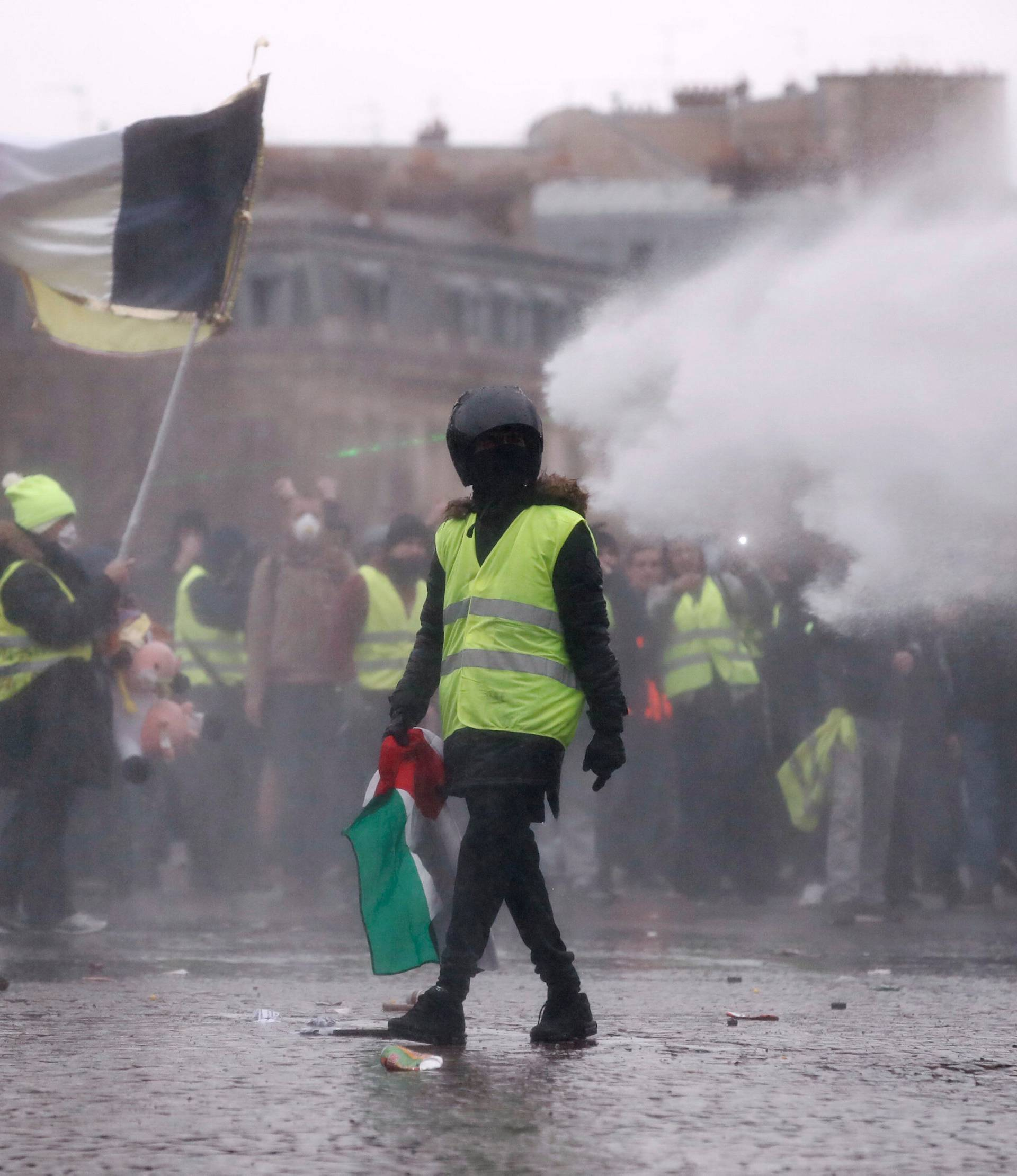"""A protester wearing a yellow vest takes part in a demonstration by the """"yellow vests"""" movement as police use a water cannon near the Arc de Triomphe in Paris"""
