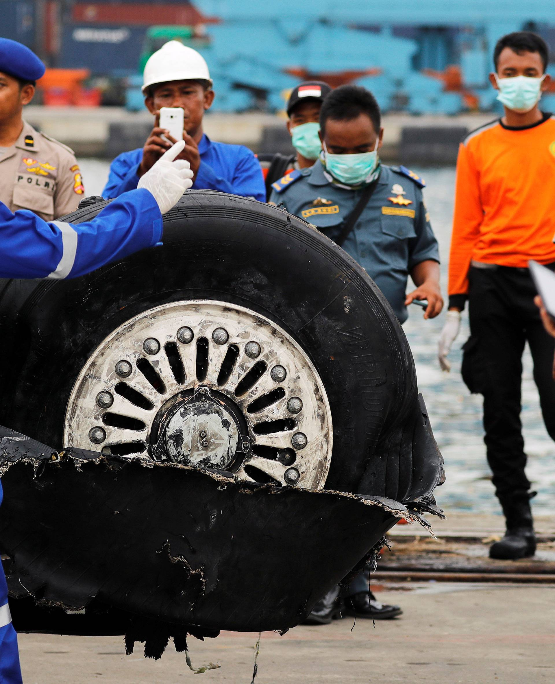 A worker assists his colleague during the lift up of a damaged tyre from the Lion Air flight JT610 jet, at Tanjung Priok port in Jakarta