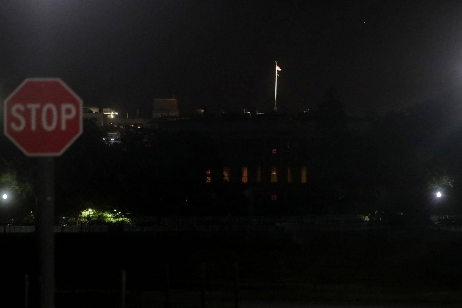A U.S. flag flies at over the darkened White House during protests against the death in Minneapolis police custody of George Floyd, in Washington