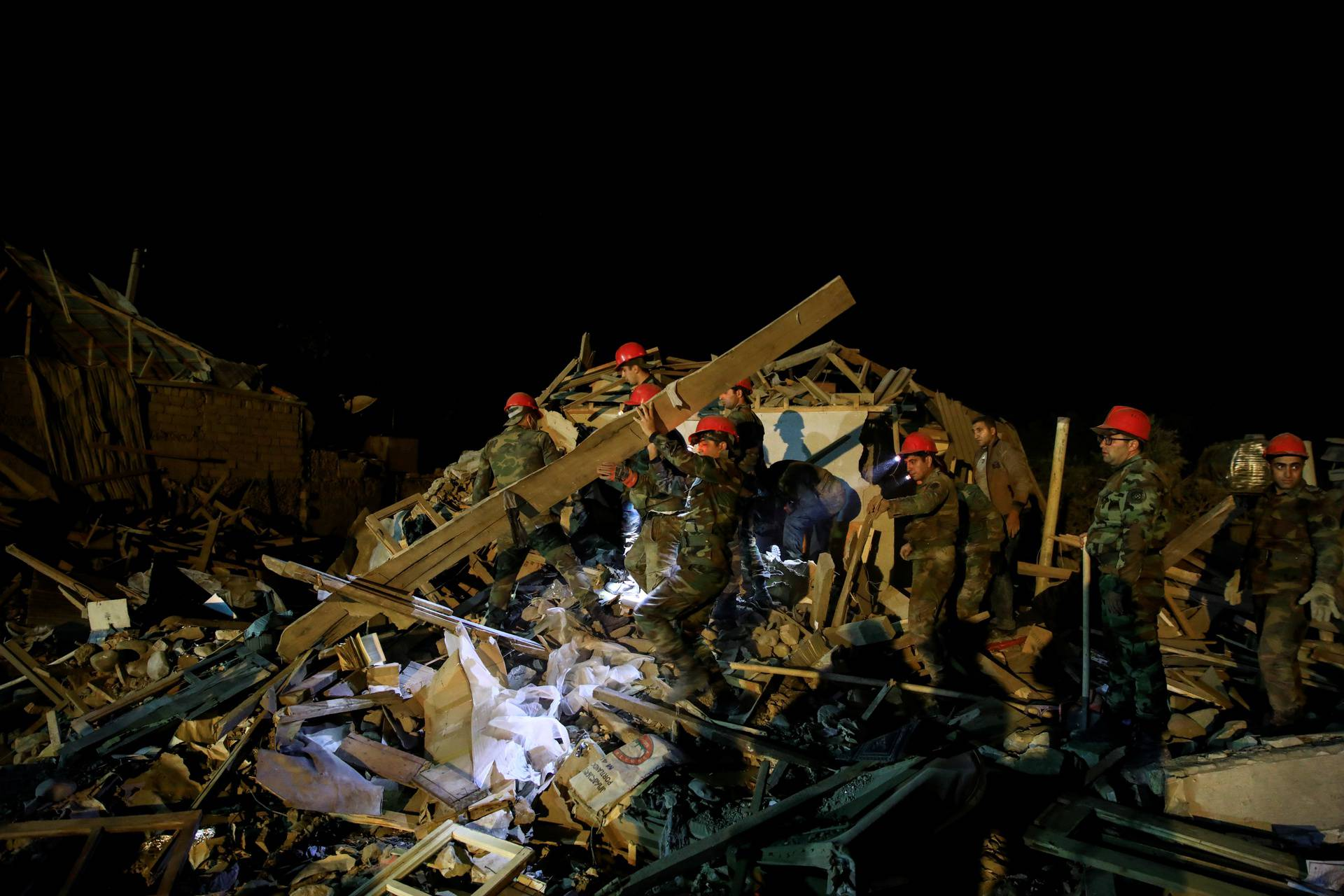 Search and rescue teams work on the blast site hit by a rocket in the city of Ganja