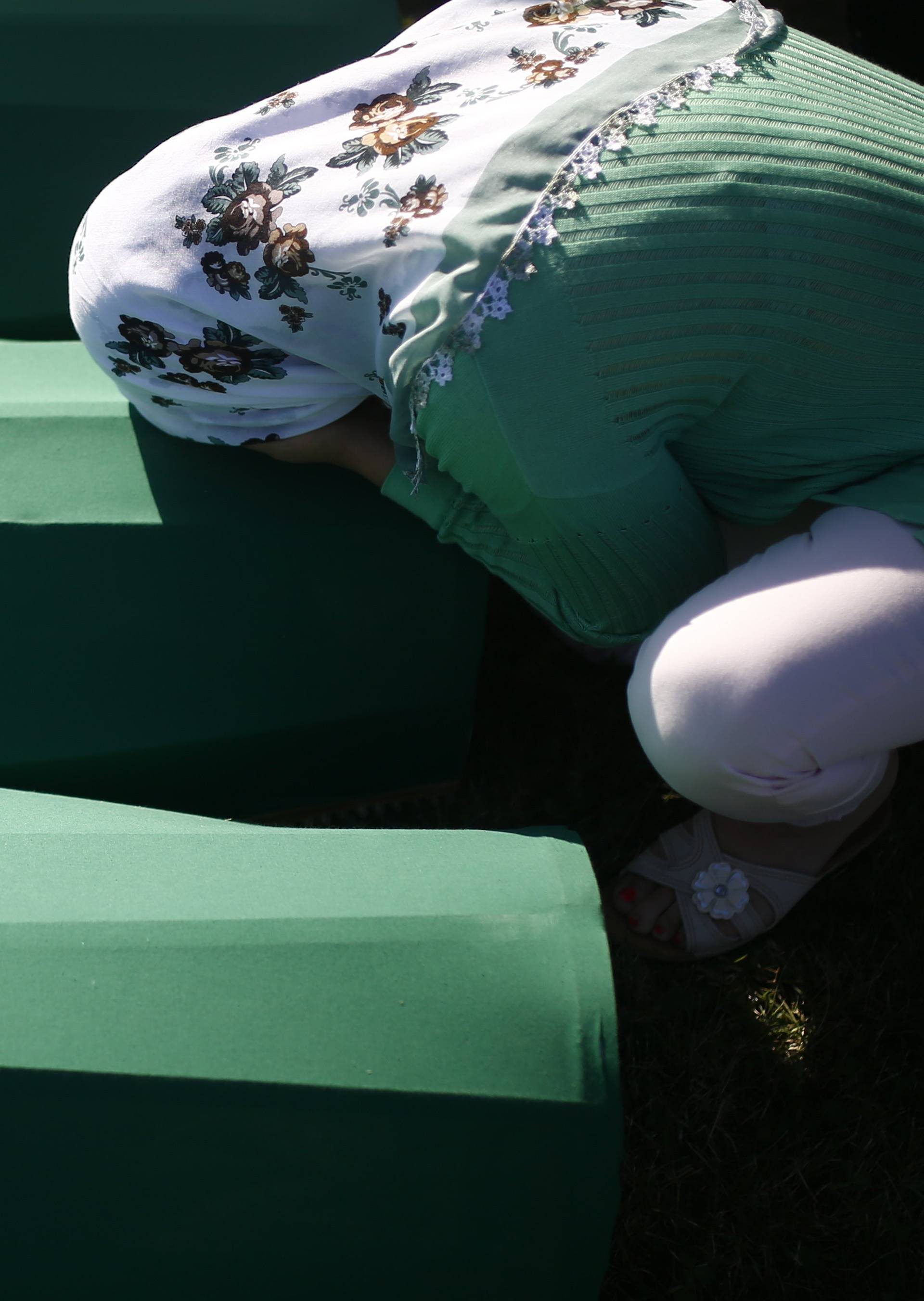 A woman mourns near coffins of her relatives, who are newly identified victims of the 1995 Srebrenica massacre, which are lined up for a joint burial in Potocari near Srebrenica