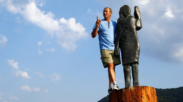 Ales Zupevc poses next to the new bronze statue of U.S. first lady Melania Trump in Rozno, near her hometown of Sevnica
