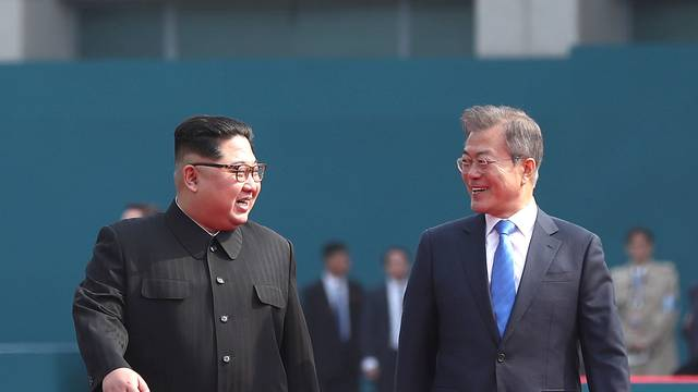 South Korean President Moon Jae-in walks with North Korean leader Kim Jong Un during their meeting at the truce village of Panmunjom