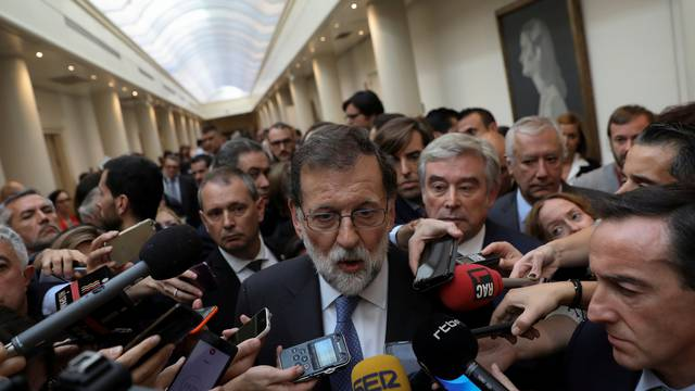 Spain's PM Rajoy talks to reporters after a plenary session at the upper house Senate in Madrid