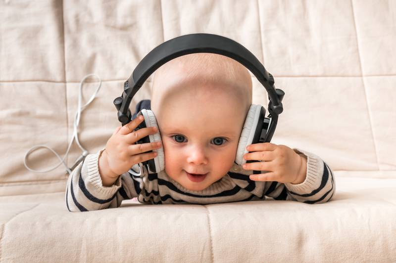 Cute baby with headphones listens to music at home