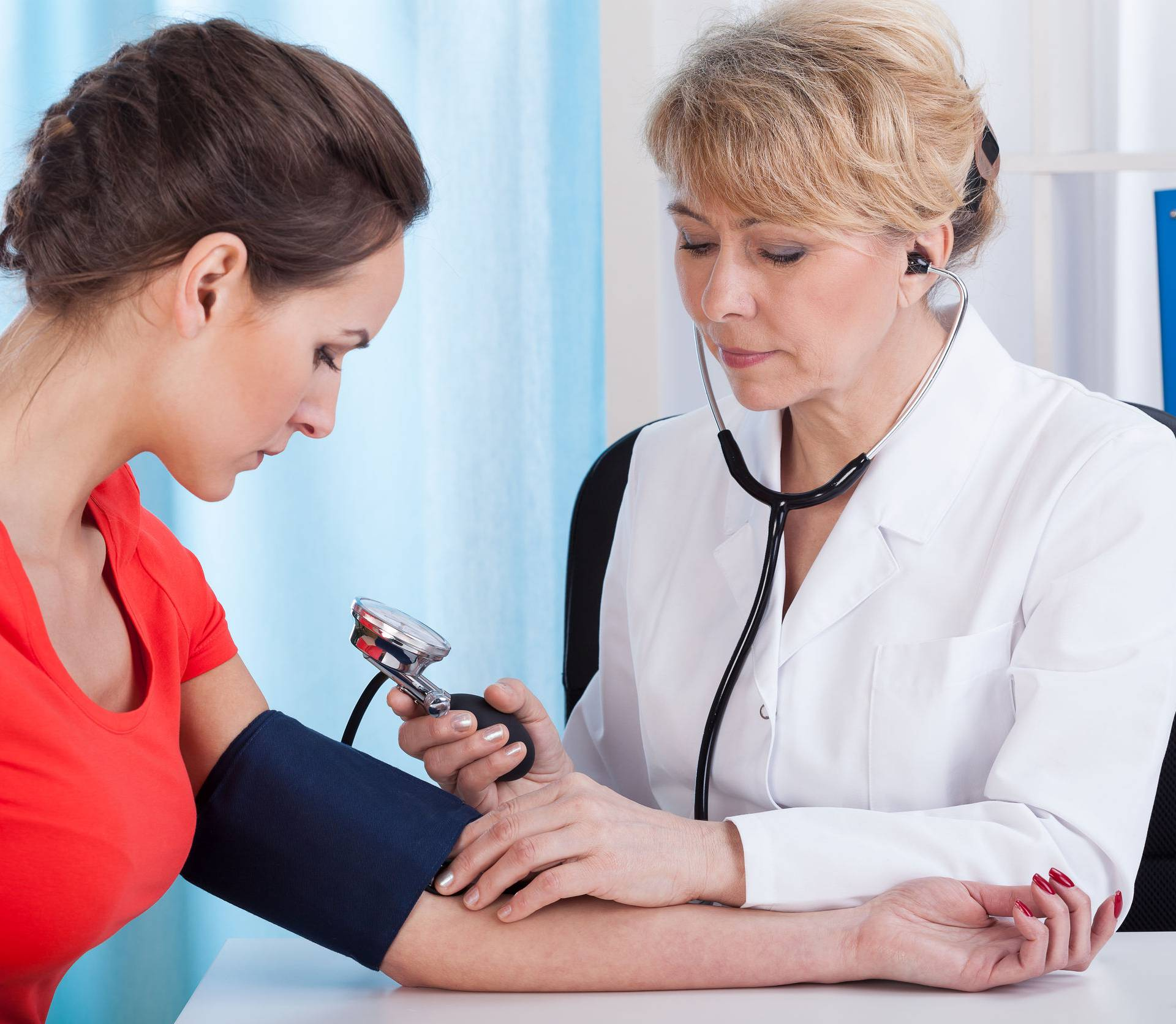 Taking blood pressure of female patient
