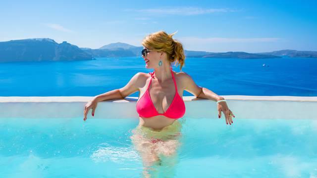 Woman in bikini relaxing in luxury outdoor pool