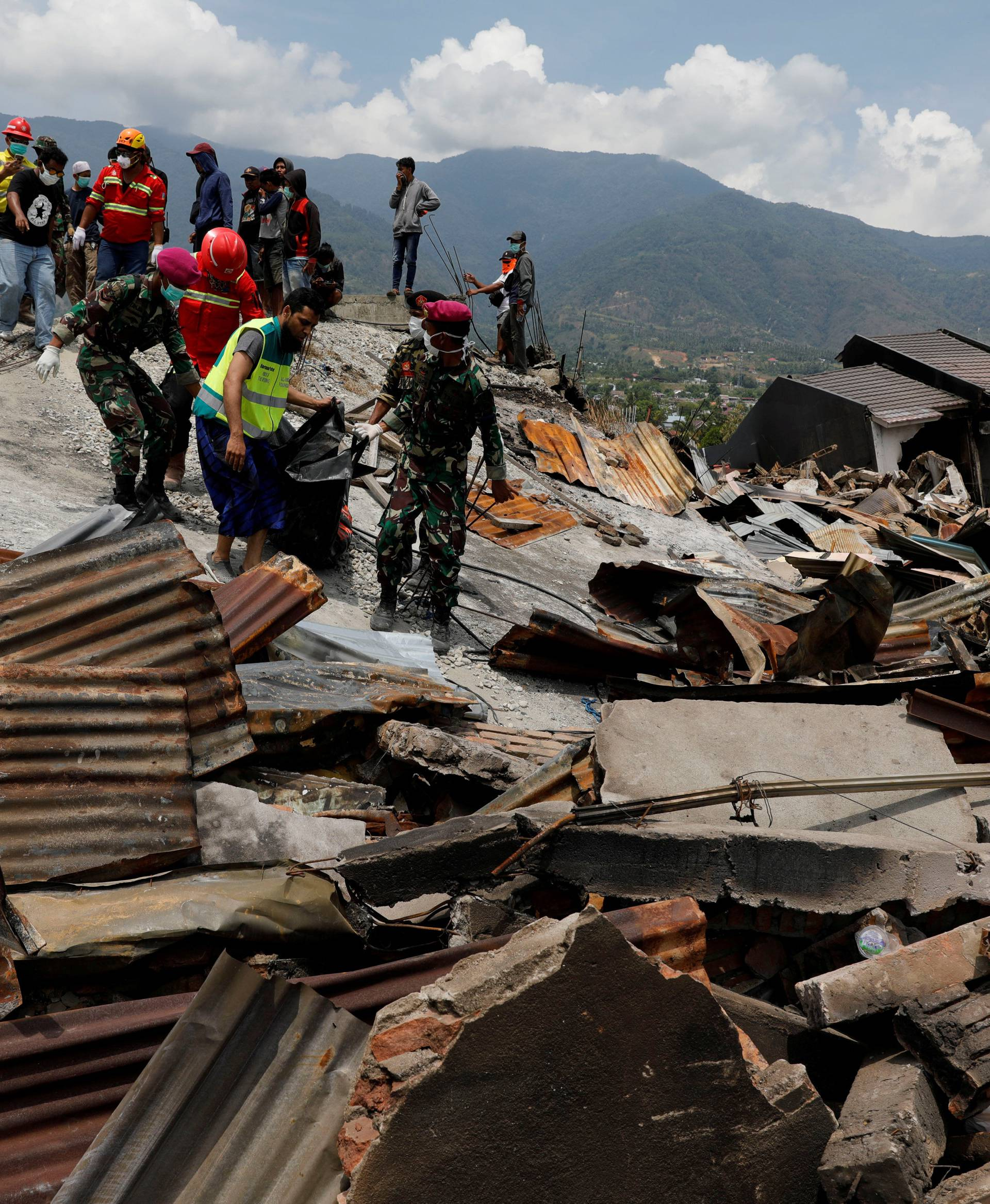 Indonesian soldiers carry a dead body from the ruins of houses after an earthquake hit Balaroa sub-district in Palu