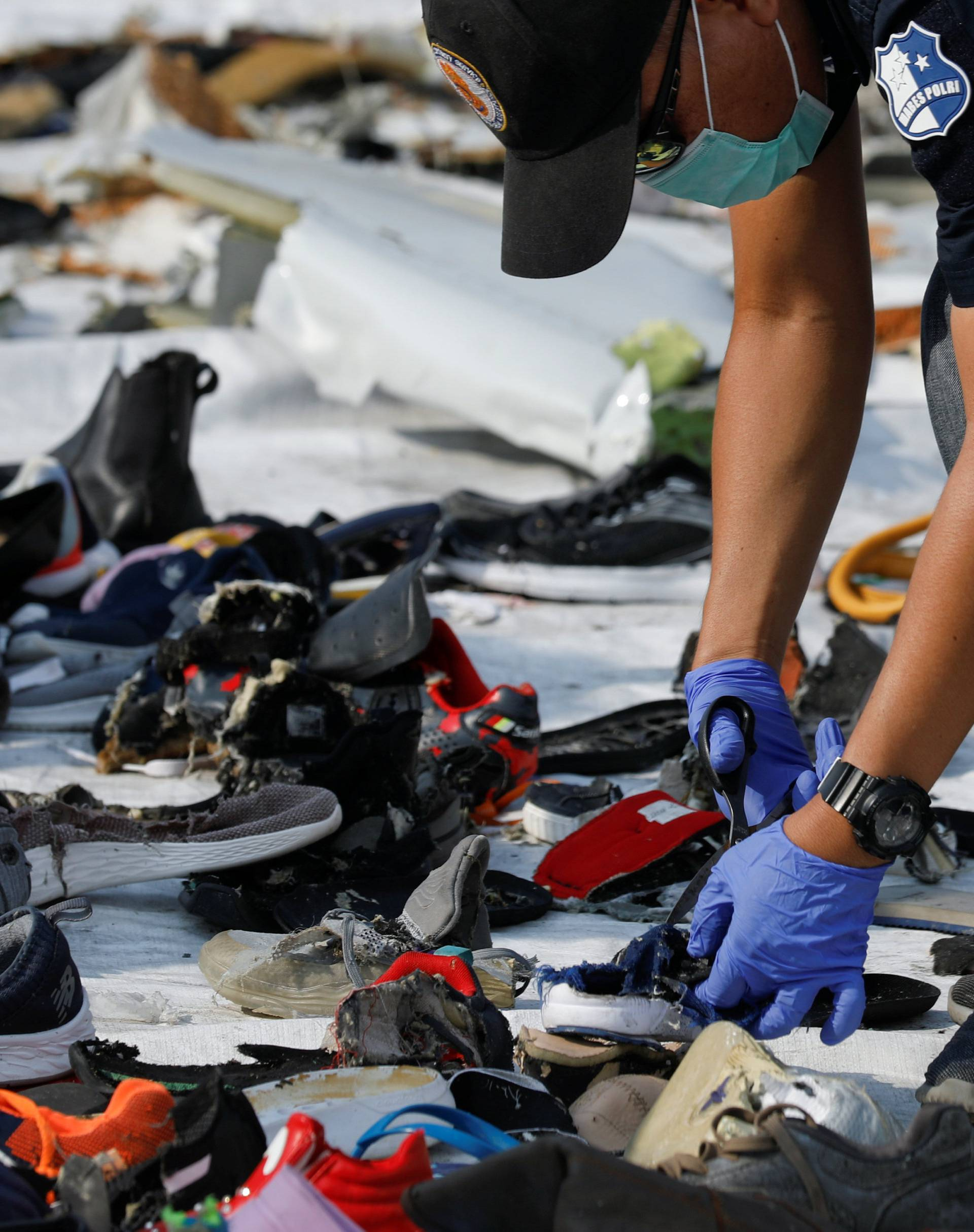 Forensic investigators collect samples of recovered belongings believed to be from crashed Lion Air flight JT610 at the Tanjung Priok port in Jakarta