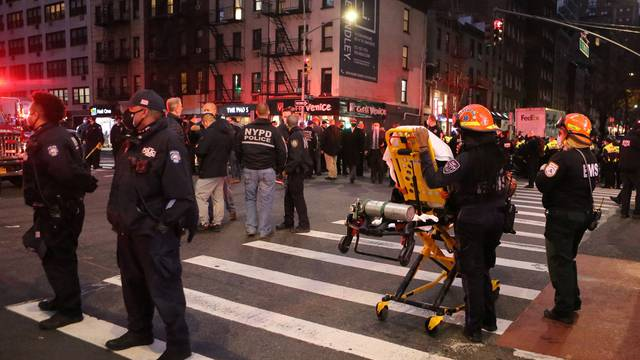 Police and EMS stand in the street at the location of a vehicle that struck multiple pedestrians on Third Avenue