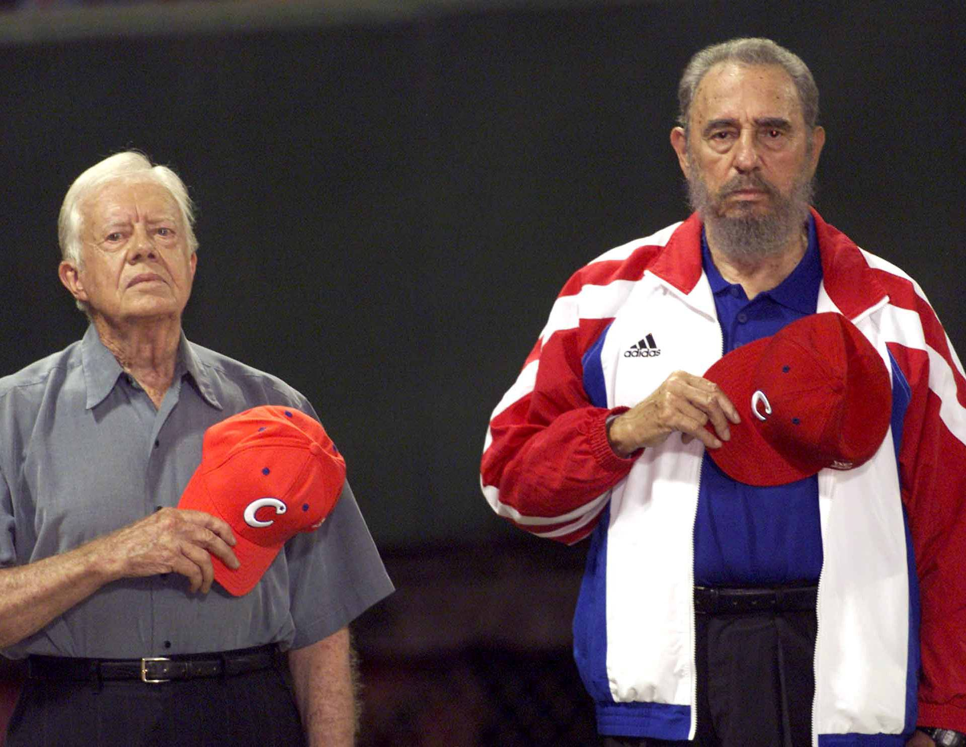 """File photo of former U.S. President Jimmy Carter and then Cuban President Fidel Castro listening to the Cuban national anthem at the baseball stadium """"Latinoamericano"""" in Havana"""