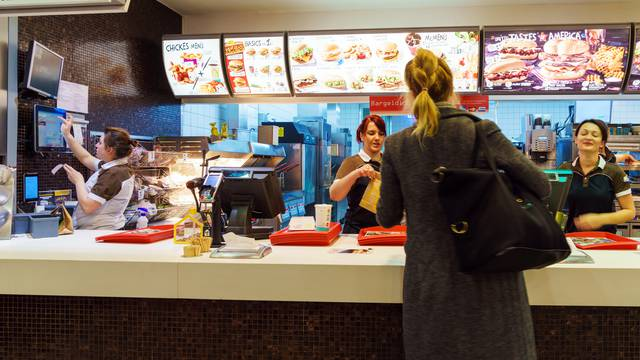 The girl receives an order in the interior of the McDonald's, Munich, Germany