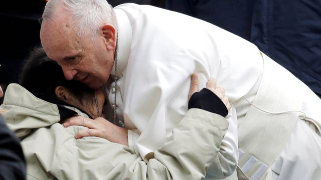 Pope Francis embrace a sick woman as he arrives to lead a Holy Mass at the Swedbank Stadion in Malmo