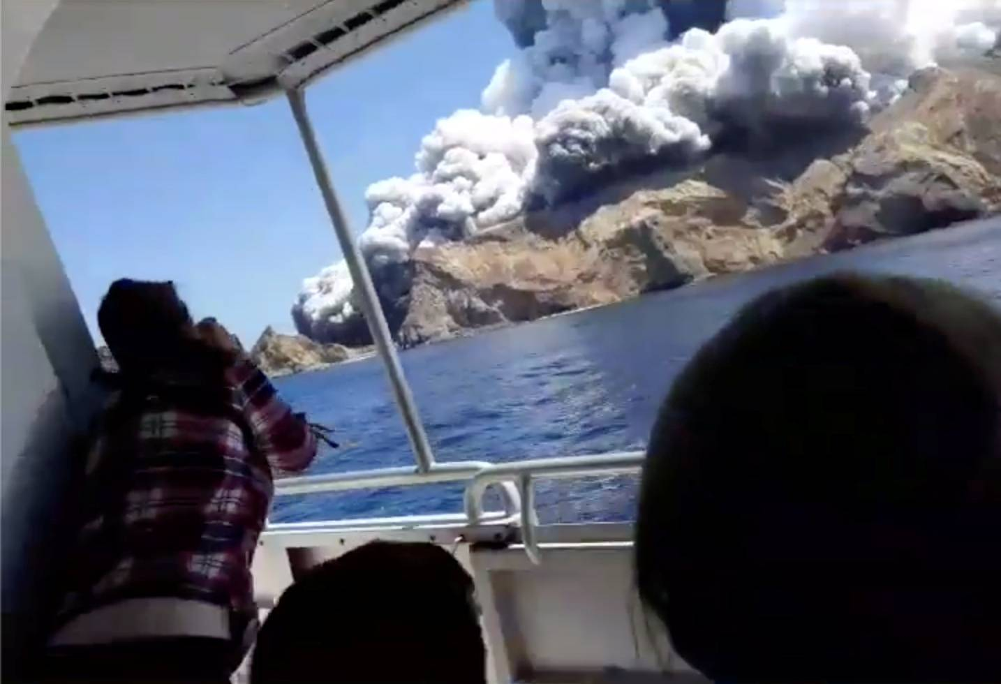 People on a boat react as smoke billows from the volcanic eruption of Whakaari, also known as White Island