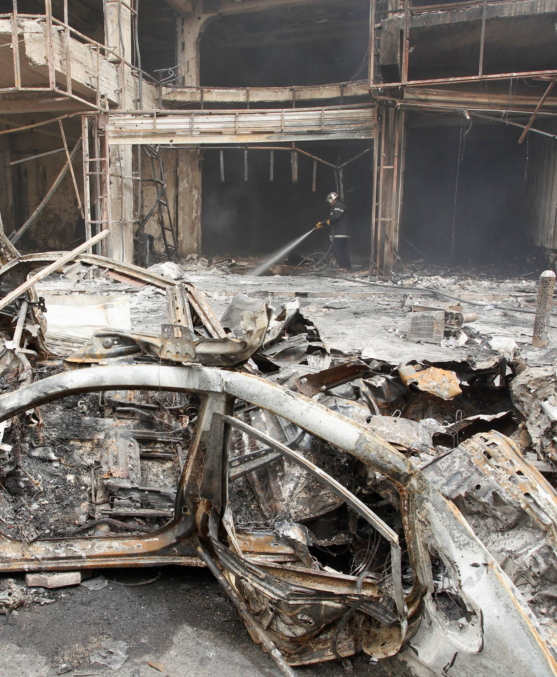 A fireman hoses down a burning building after a suicide car bomb occurred in the Karrada shopping area in Baghdad, Iraq