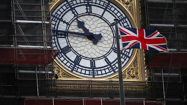 Union Jack flag flutters in front of Big Ben's clock face in London
