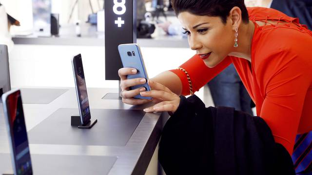 A woman takes a picture of the Samsung Galaxy S8+ smartphone at the introduction of the Galaxy S8 and S8+ smartphones during the Samsung Unpacked event in New York City