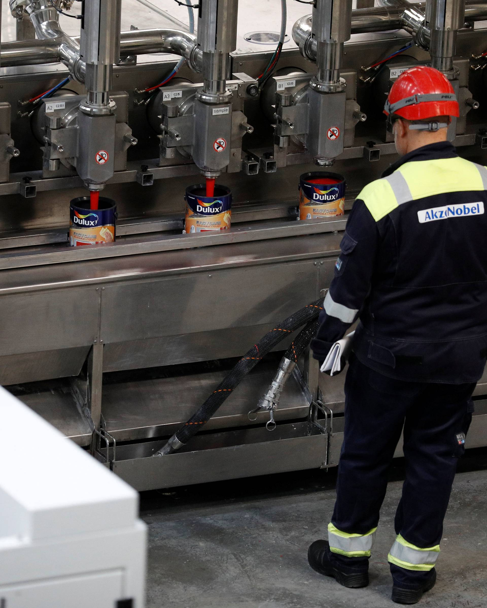 Workers look on as Dulux paint cans are filled on the production line inside AkzoNobel's new paint factory in Ashington, Britain