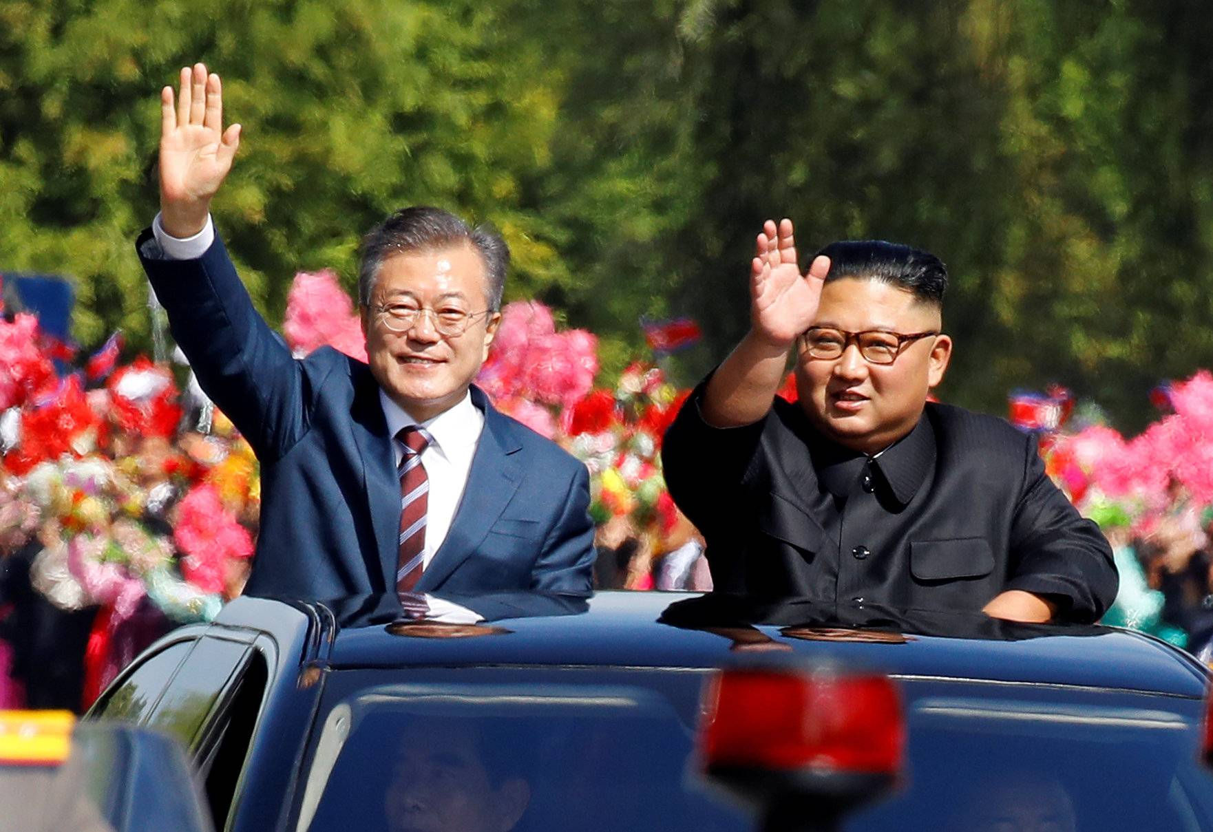 South Korean President Moon Jae-in and North Korean leader Kim Jong Un wave during a car parade in Pyongyang