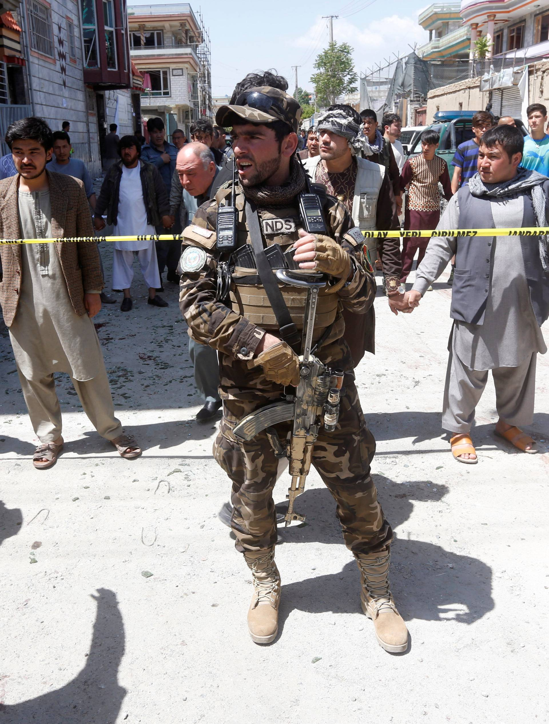 An Afghan security forces mamber stands guard at the site of a suicide bomb attack in Kabul