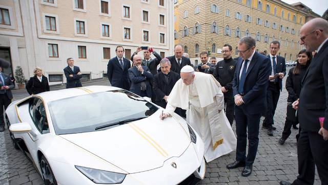Pope Francis signs a Lamborghini Huracan prior to his Wednesday general audience in Saint Peter's square at the Vatican