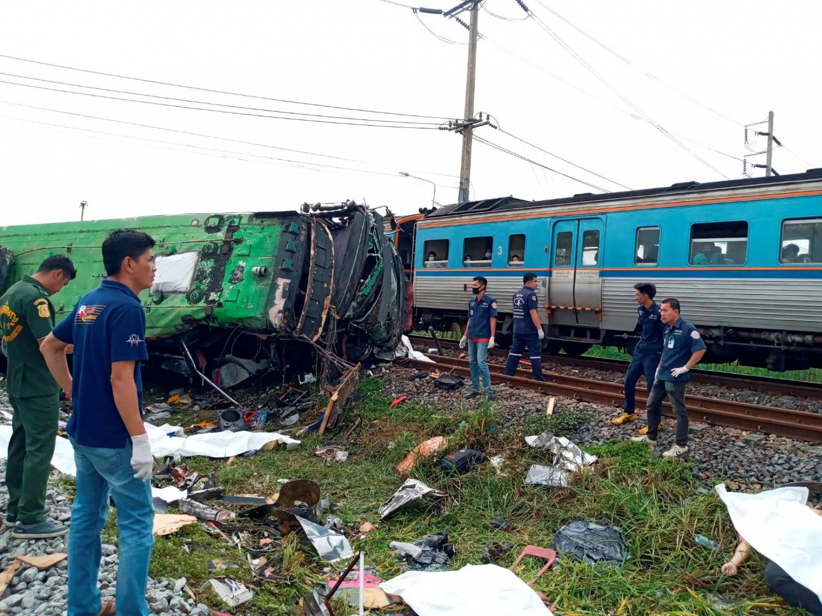 Rescue workers stand at the crash site where a train collided with a paseengers bus in Chacheongsao province in central Thailand