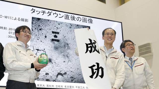 JAXA associate professor Yuichi Tsuda holds a banner reading 'success' in front of an image of the Hayabusa 2 space probe's landing on the Ryugu asteroid in Sagamihara