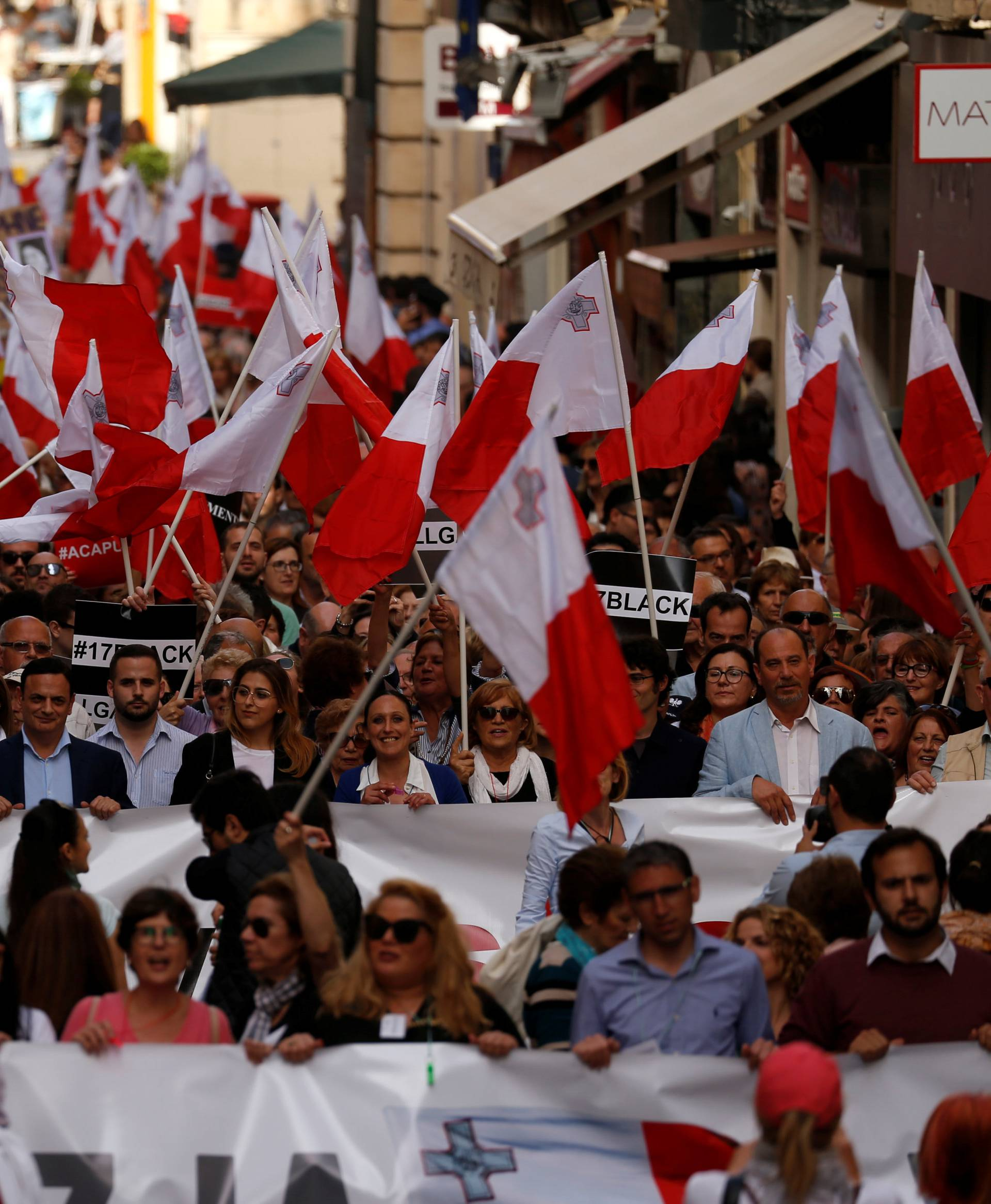 People carry Maltese flags during a protest against government corruption in light of the revelations in the Daphne Project, in Valletta