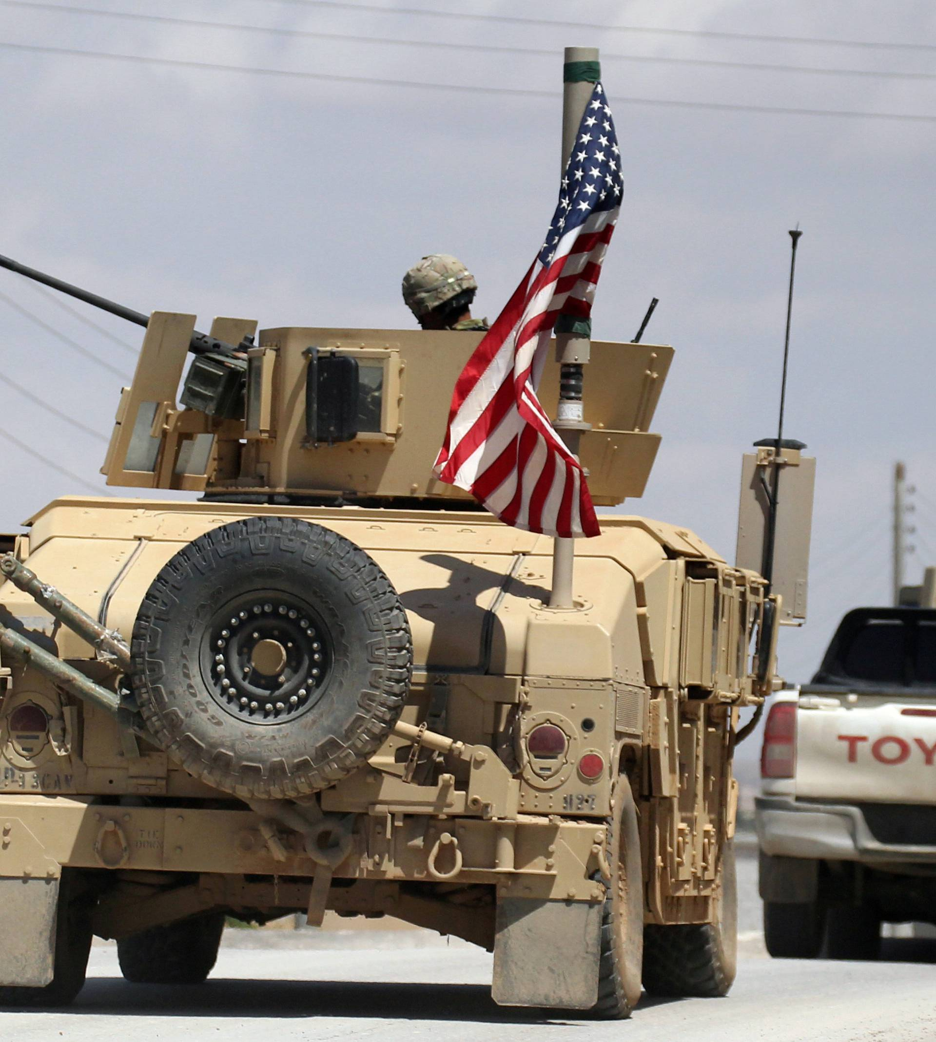 FILE PHOTO: The U.S. flag flutters on a military vehicle in Manbej countryside