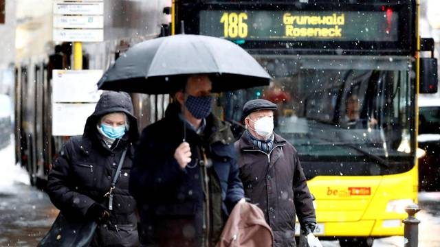 FILE PHOTO: People wear face masks as they walk past a bus in Berlin