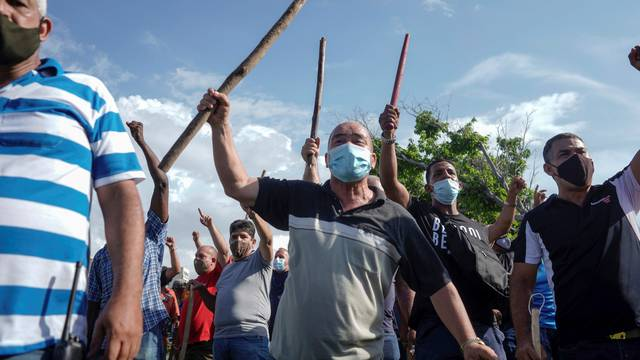 Plain clothes police and government supporters react during protests against and in support of the government, in Havana
