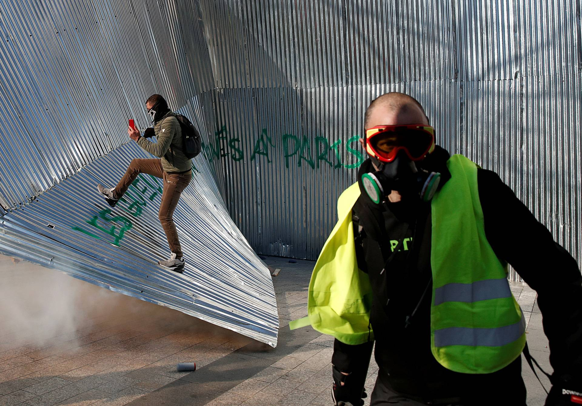 "Protester wearing a yellow vest walks in front of demolished metal fencing during a demonstration by the ""yellow vests"" movement in Paris"