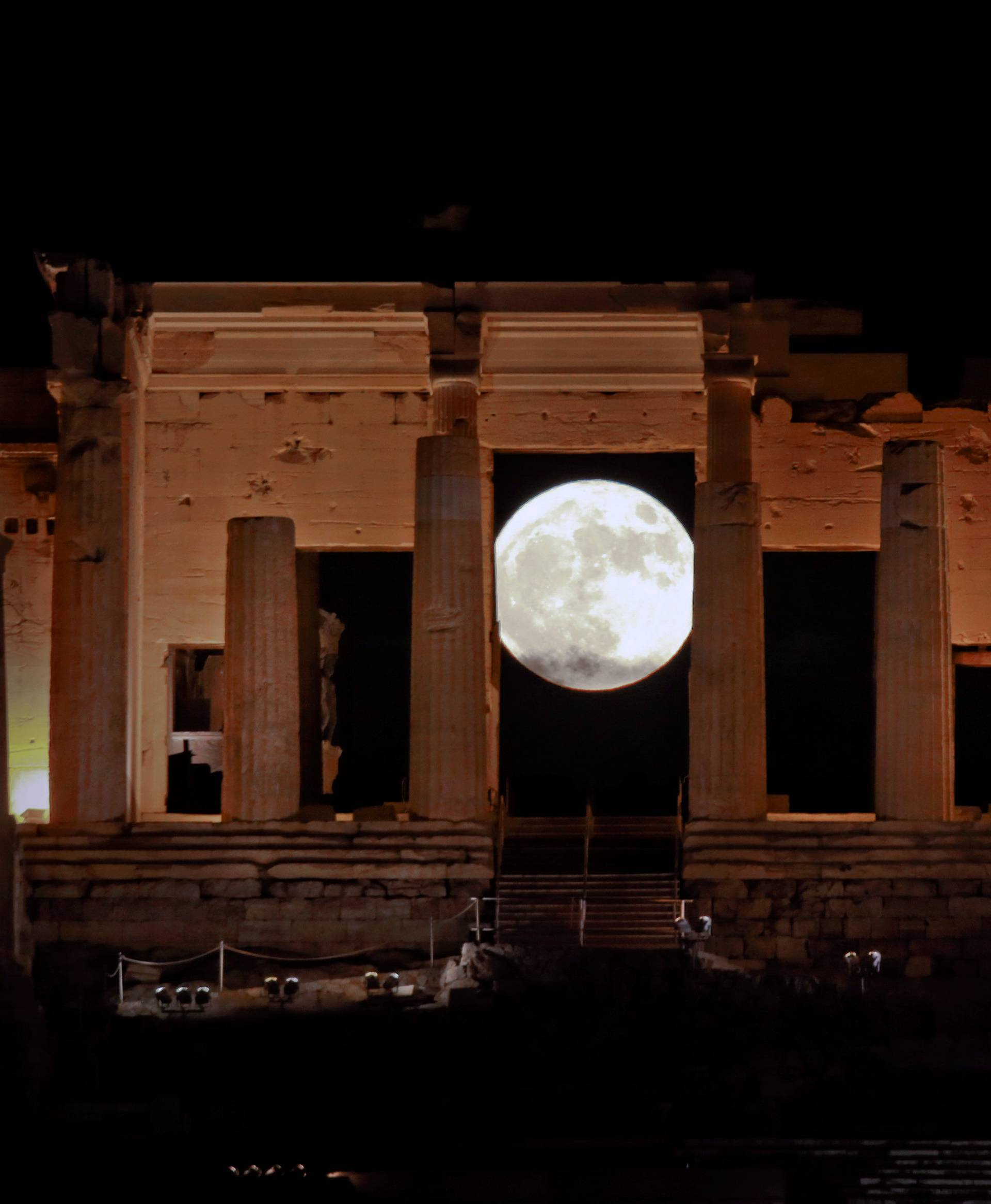 "A rising ""supermoon"" is seen through the Propylaea, the ancient Acropolis hill gateway, in Athens"