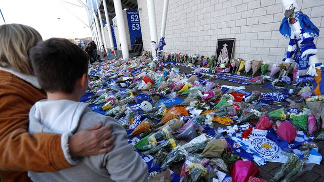 Leicester City football fans pay their respects outside the football stadium, after the helicopter of the club owner Thai businessman Vichai Srivaddhanaprabha crashed when leaving the ground on Saturday evening after the match, in Leicester