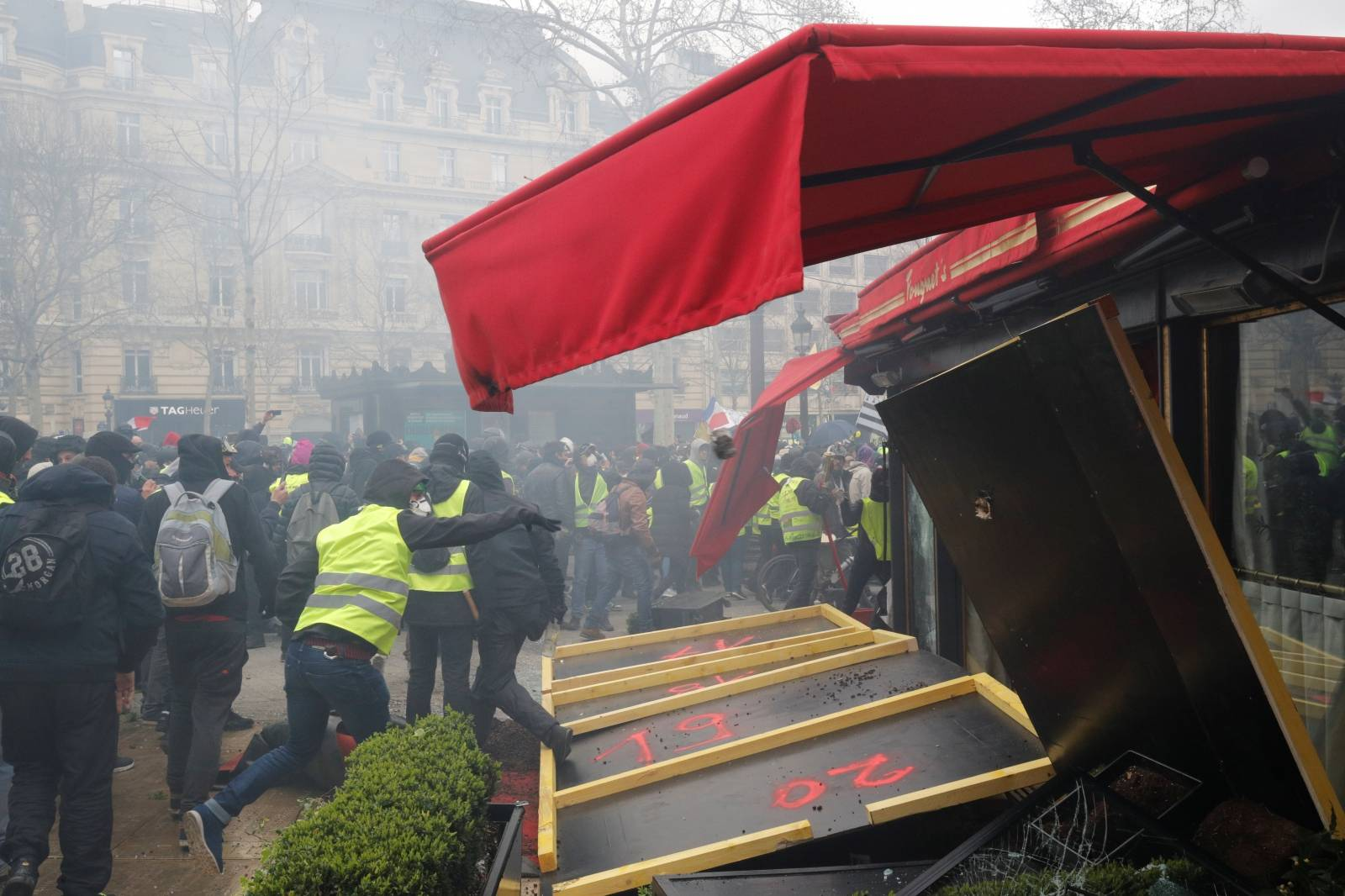 """A protester throws a stone during a demonstration by the """"yellow vests"""" movement in Paris"""