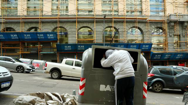 A man looks inside a garbage container on Corrientes avenue in Buenos Aires' financial district