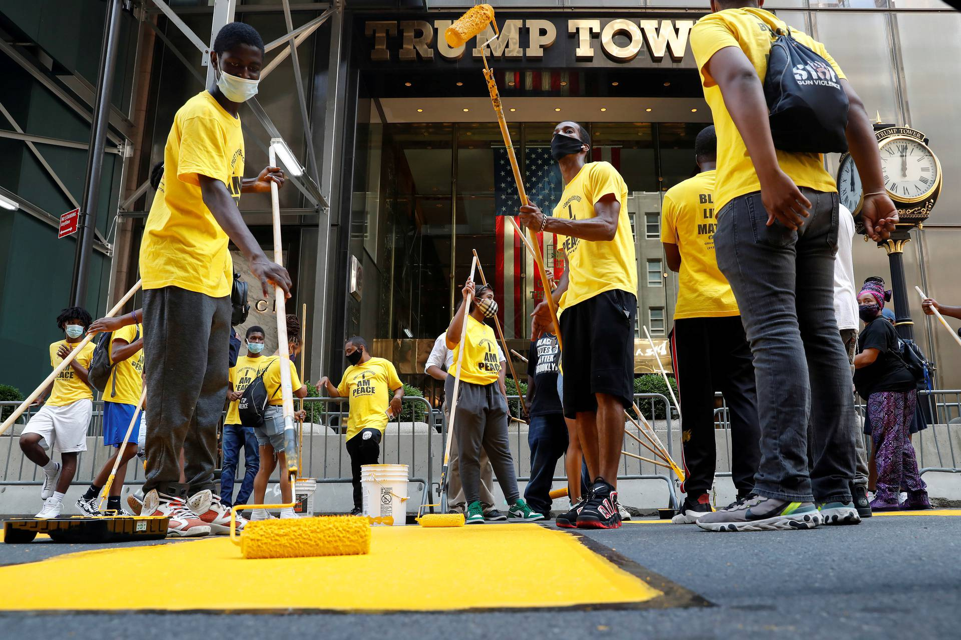 """People paint a """"Black Lives Matter"""" along 5th avenue outside Trump Tower in New York City"""