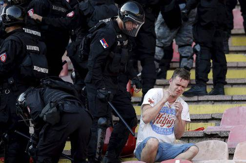 An injured Red Star Belgrade fan sits during clashes with riot police in the stadium before their Serbian Superliga soccer match against Partizan Belgrade in Belgrade