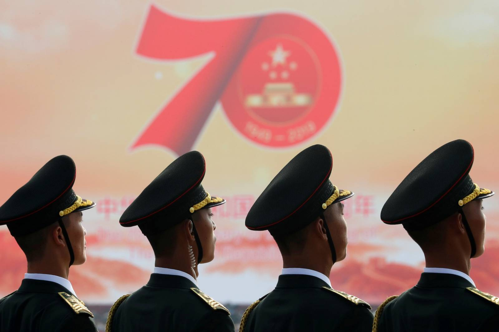 Soldiers of People's Liberation Army (PLA) are seen in front of a sign marking the 70th founding anniversary of People's Republic of China before a military parade on its National Day in Beijing