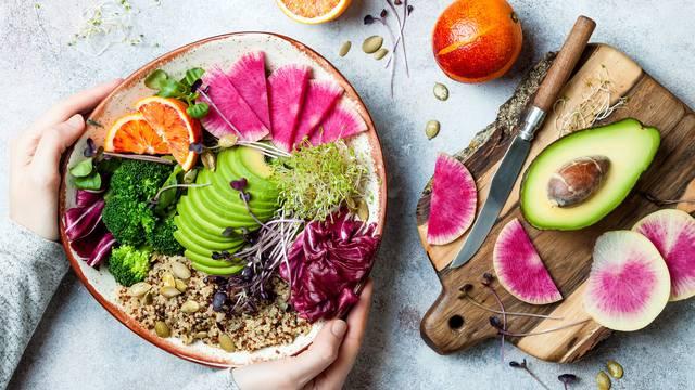 Girl holding vegan, detox Buddha bowl with quinoa, micro greens, avocado, blood orange, broccoli, watermelon radish, alfalfa seed sprouts.