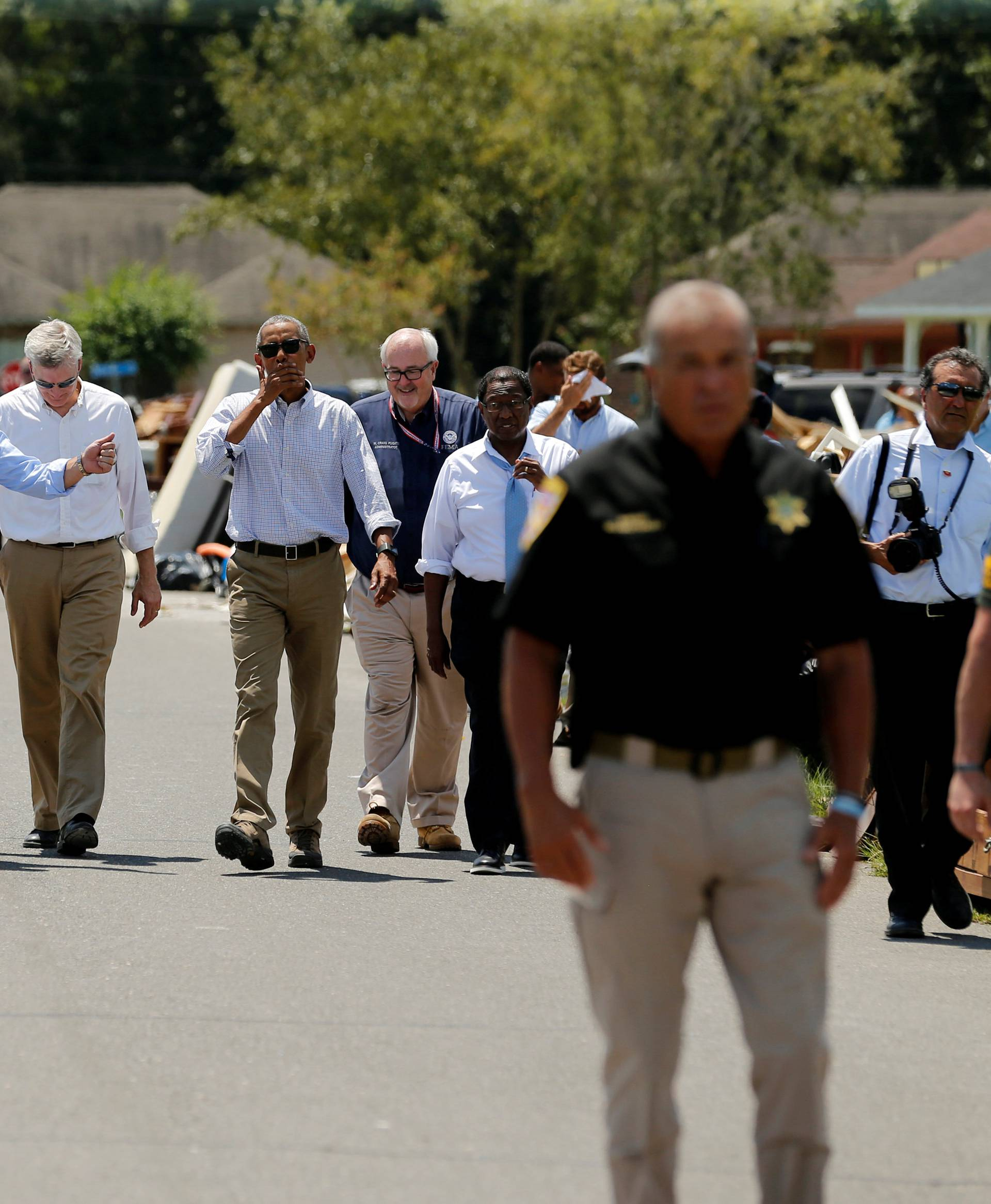 U.S. President Barack Obama tours a flood-affected neighborhood with U.S. Senator David Vitter, Louisiana Governor John Bel Edwards and U.S. Senator Bill Cassidy in Zachary