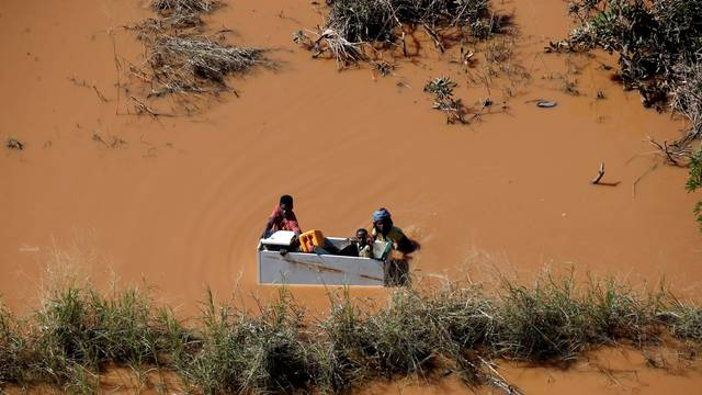 A child is transported on a fridge during floods after Cyclone Idai, in Buzi, outside Beira