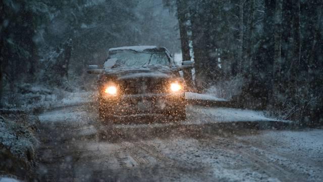 Sport utility vehicle driving in a snow storm near Sitka, Alaska, USA