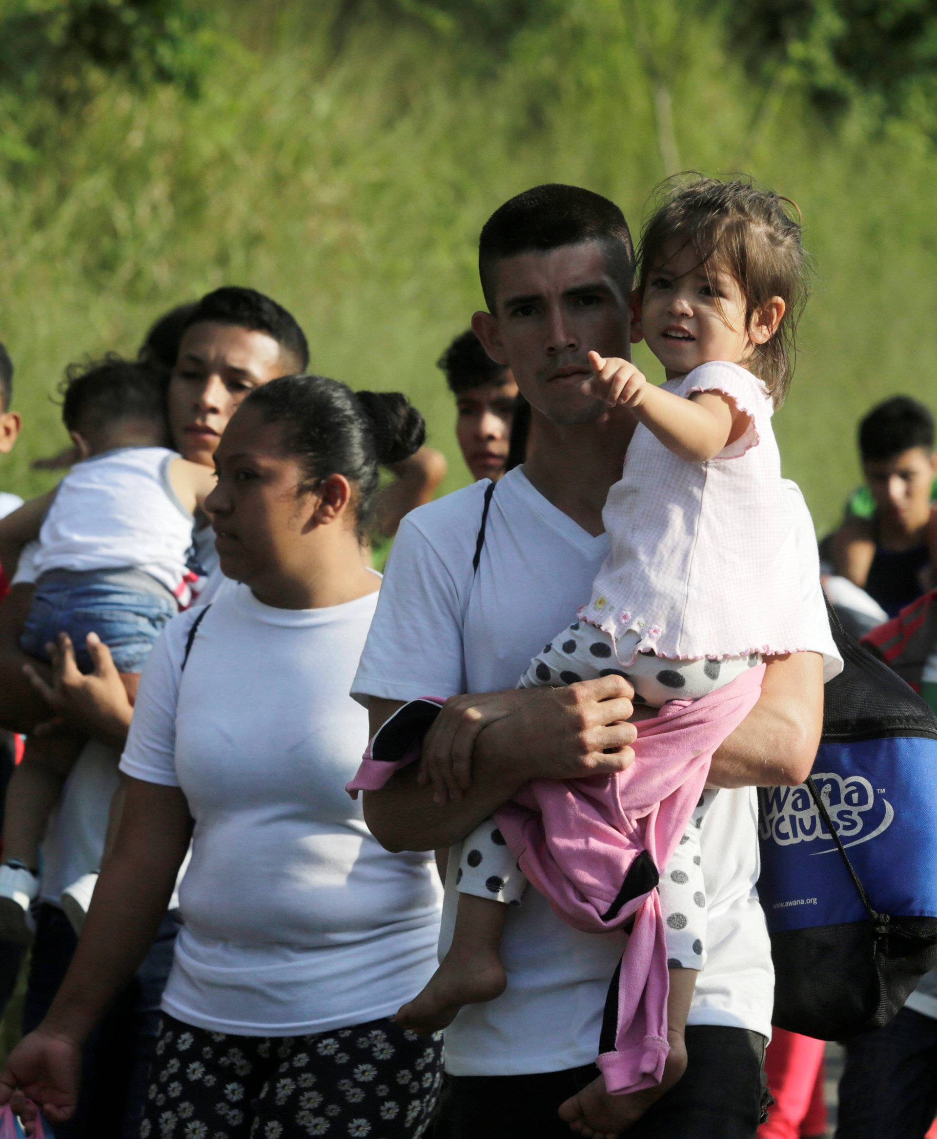 A man carries a child along other Hondurans fleeing poverty and violence, as they move in a caravan toward the United States, in San Pedro Sula