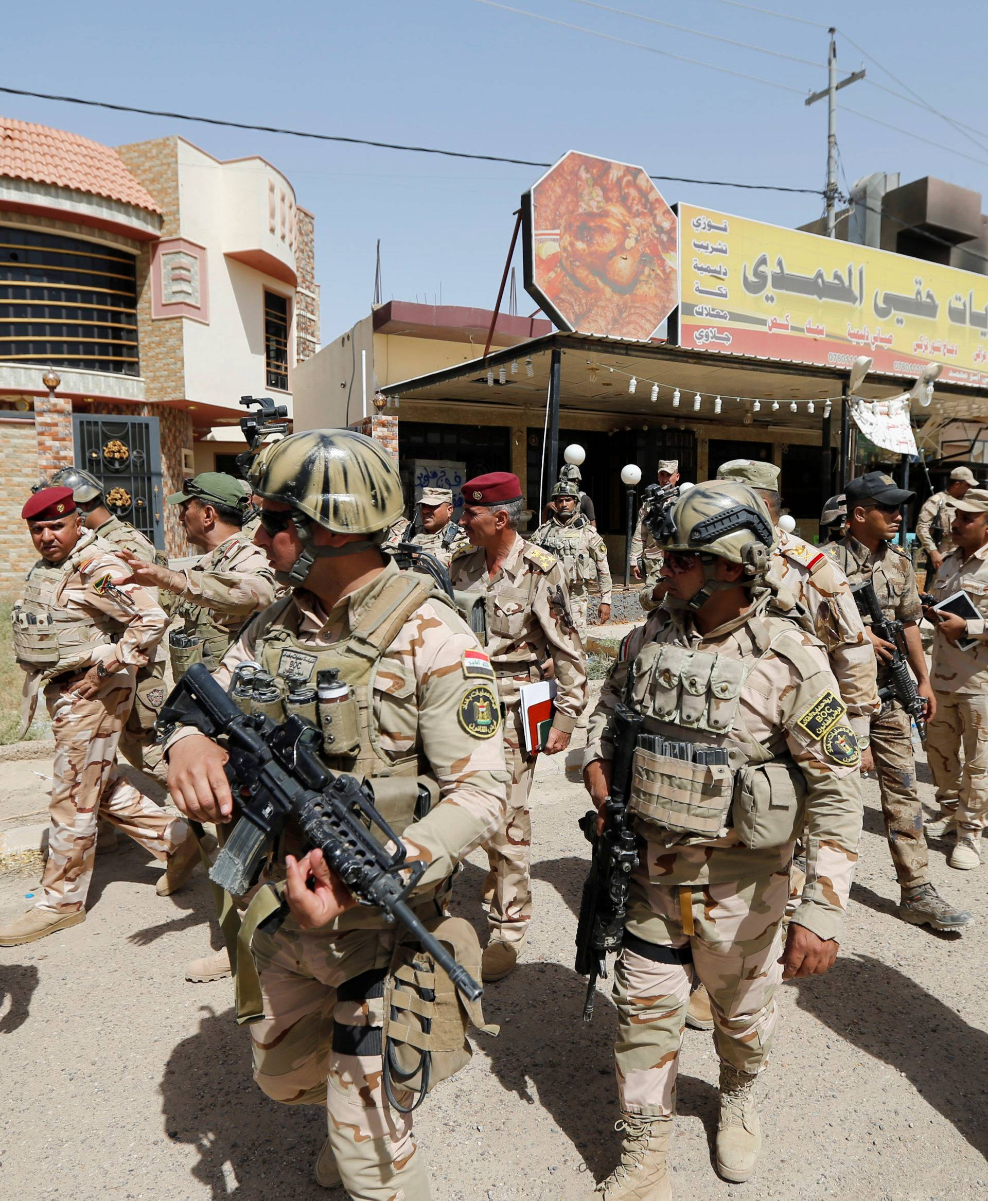 Iraqi army soldiers walk with their weapons in center of Falluja