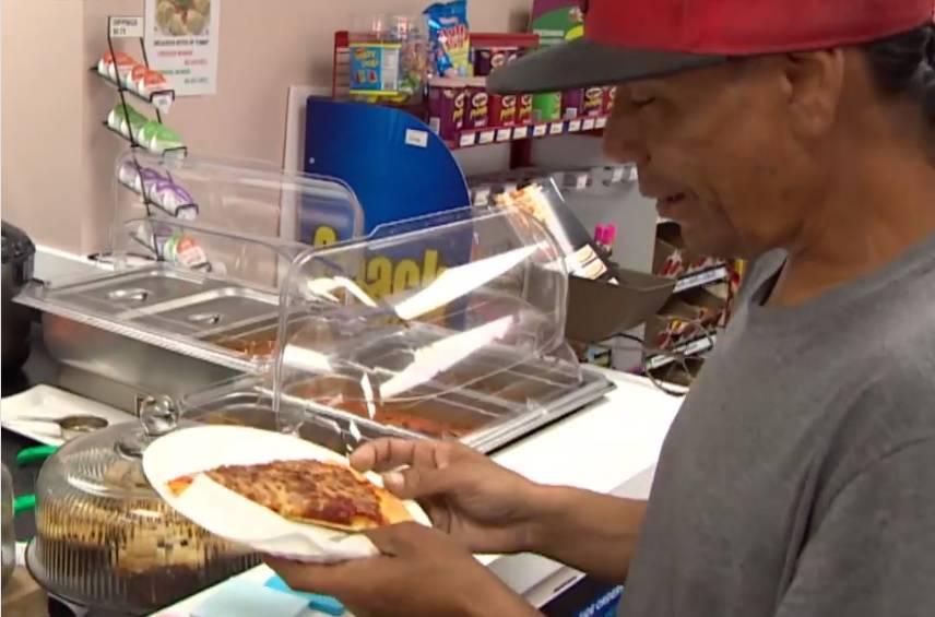 Kupci plate komad pizze koju potom uzimaju siromašni ljudi