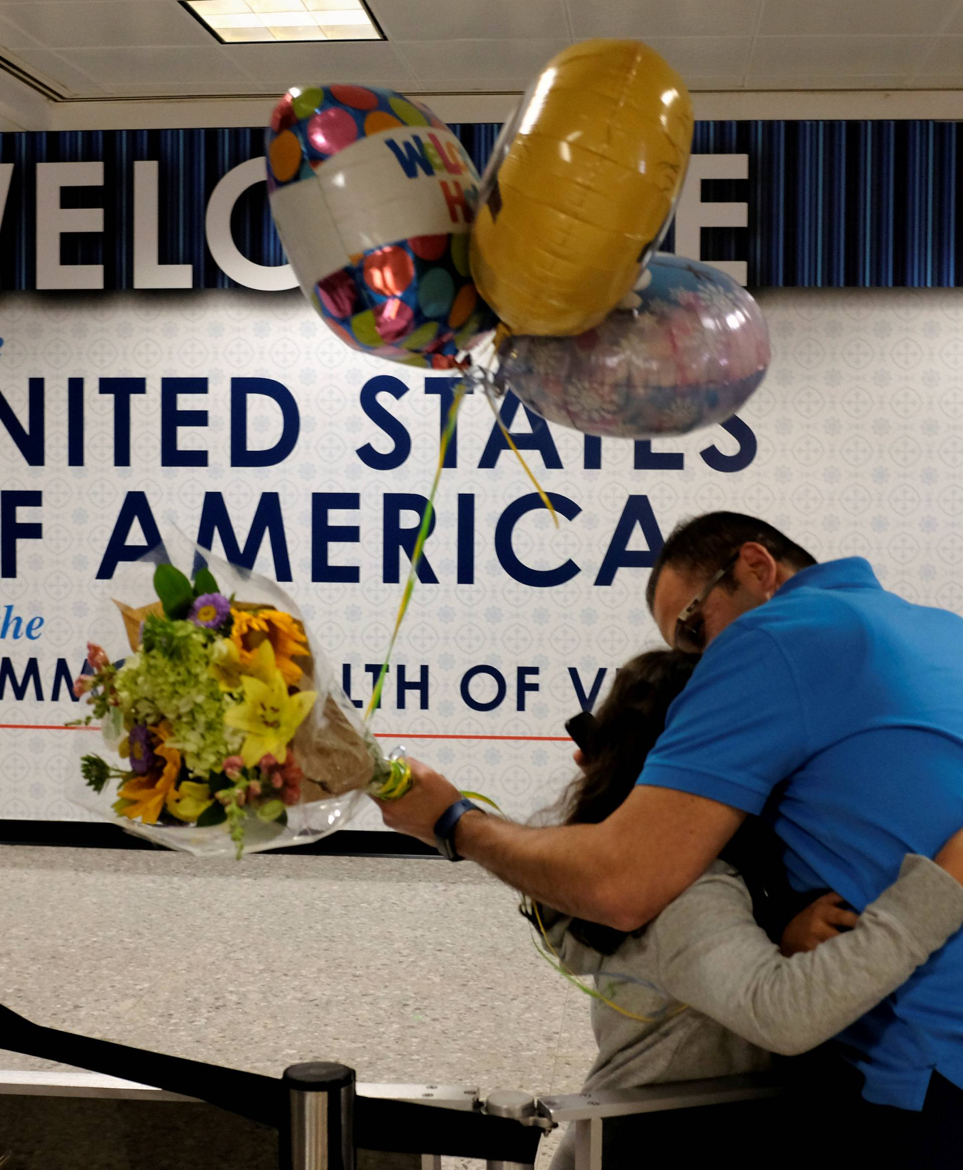 FILE PHOTO: Ahmed Khalil hugs his daughters as they arrive at Washington Dulles International Airport in Dulles Virginia