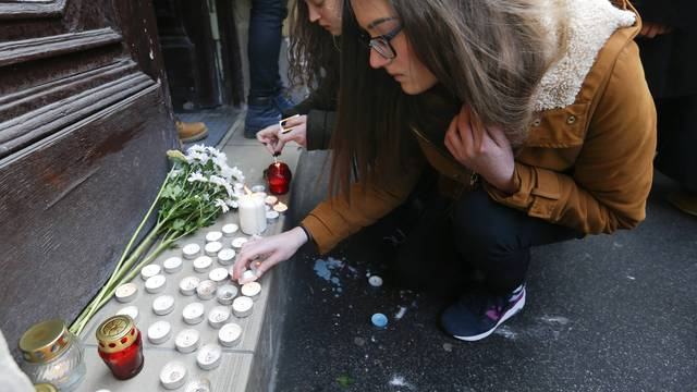 People light candles in front of a school building in Budapest
